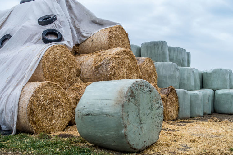 Stack of hay bales on field against sky