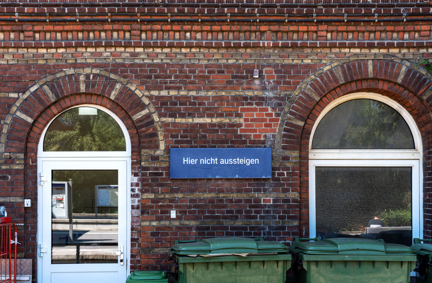 Attention Letters Signal Architecture Brick Brick Wall Building Building Exterior Built Structure Communication Day Door Entrance Information No People Outdoors Script Seat Sign Text Wall Wall - Building Feature Waste