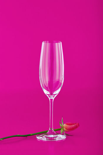 Close-up of wineglass against pink background