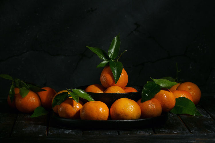Home grown organic tangerines with leaves over a black wooden board. Dark Rustic Style Detox Natural Orange Citrus Fruit Food Food And Drink Freshness Fruit Healthy Healthy Eating Juicy Leaf Leaves Mandarin Tangerine Vitamin