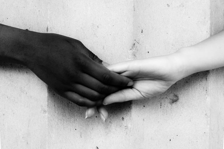 Cropped image of friends holding hands against wall