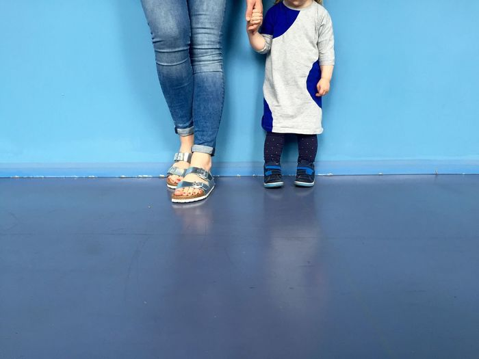 Low section of woman with daughter standing on floor against wall