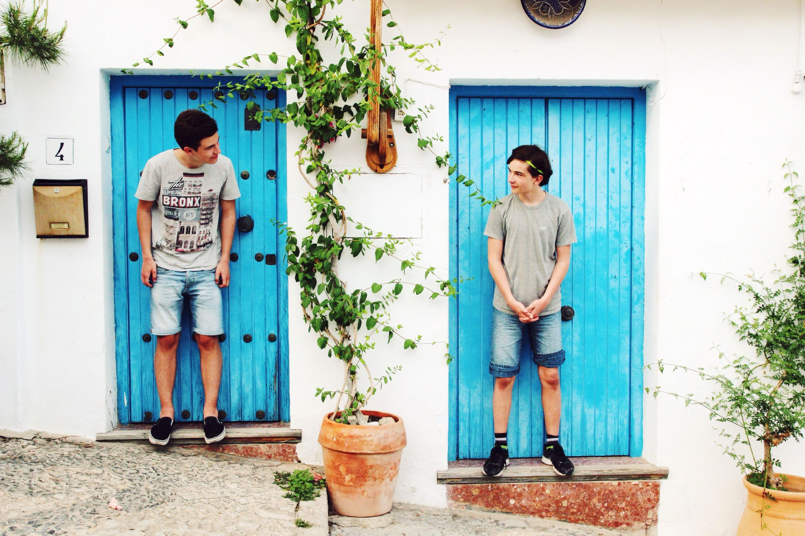 lifestyles, leisure activity, full length, casual clothing, built structure, architecture, house, person, standing, building exterior, childhood, boys, elementary age, door, day, blue, sitting, potted plant