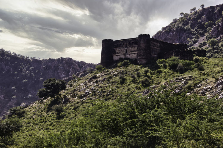 Mountains surrounding abandoned ruined fort in a place named ajabgarh on a way to bhangarh