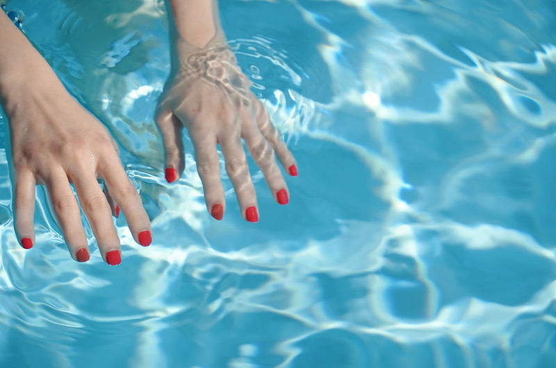 Low section of woman standing in swimming pool