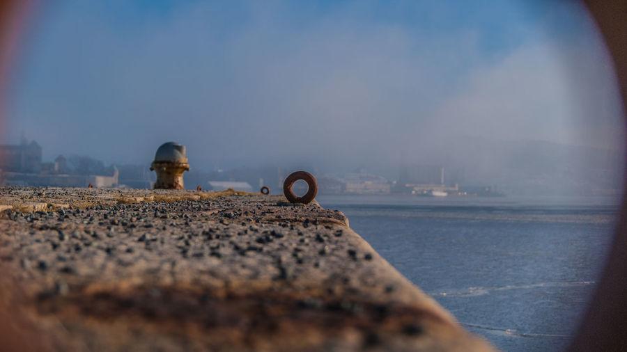 Lifebelt on pier by sea