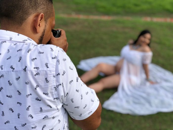 Man photographing pregnant woman on field
