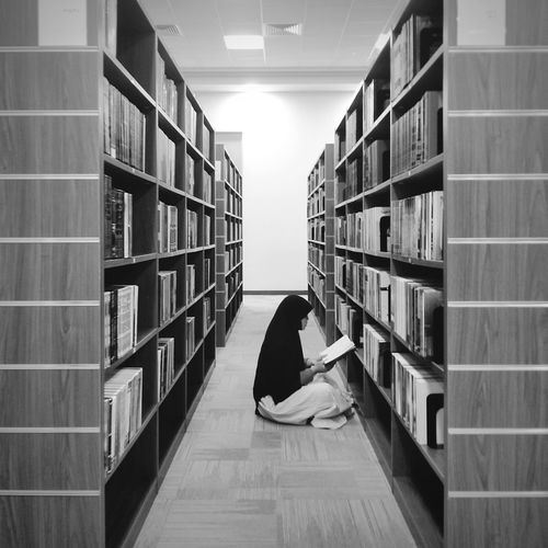 Woman reading book while sitting amidst bookshelves at library