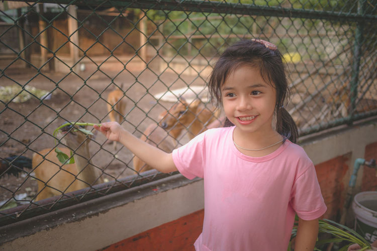 Portrait of a smiling girl looking through fence