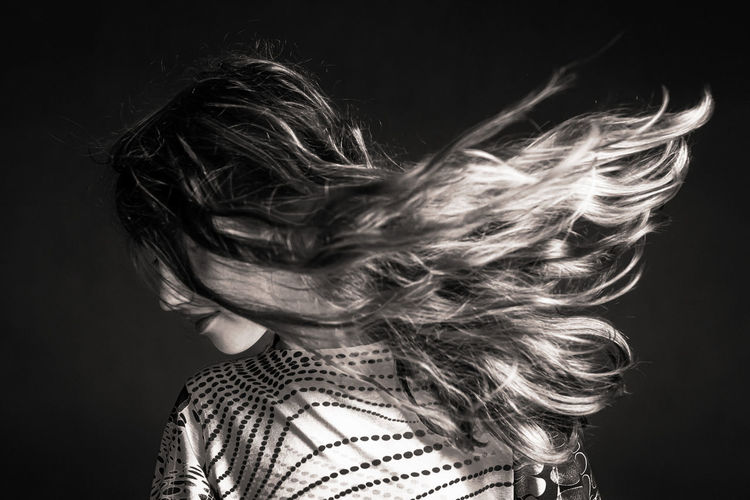 Woman with long hair against black background