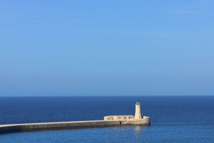 Scenic view of a breakwater and lighthouse on the mediterranean sea against a clear blue sky
