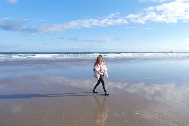 Side view of girl walking at beach against sky