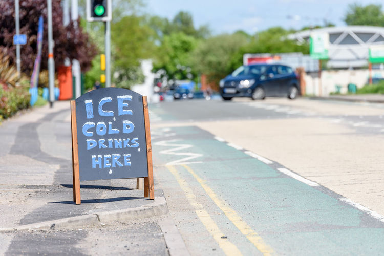 Day view Ice Cold Drinks Here wooden sign on British sidewalk British Drinks Here Belongs To Me Ice Road Sign Sunny Board Chalkboard Cold Day Uk Wooden