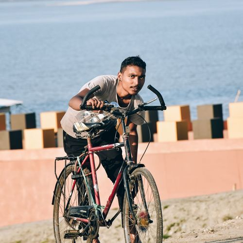 Young man riding bicycle on sea shore