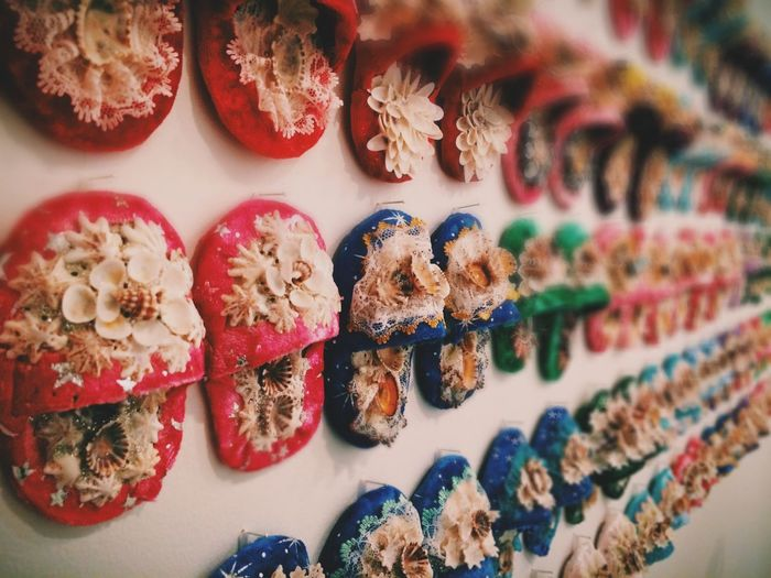 Multi colored slippers hanging on wall for sale