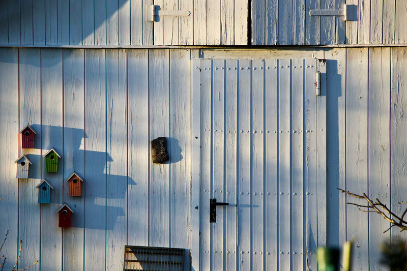 Full frame shot of white wooden wall with bird houses