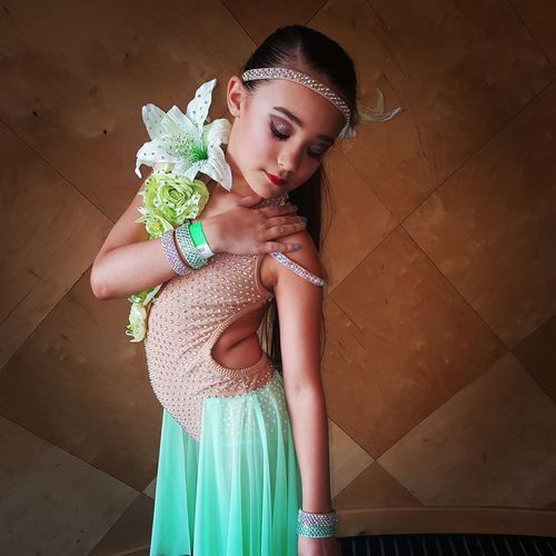 Girl In Dress Standing Against Wall At Home