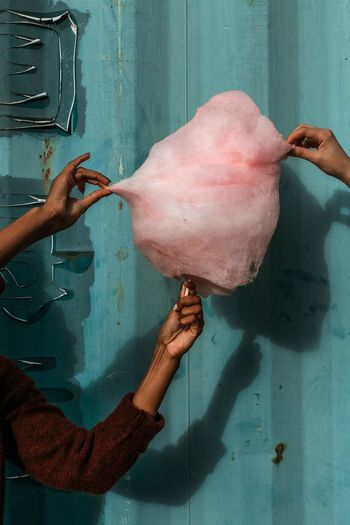 Cropped image of people holding cotton candy against corrugated iron