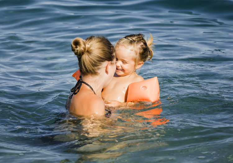 Mother enjoying with daughter in sea during summer