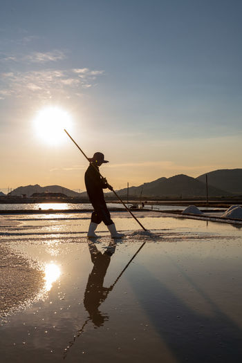 The daily activities in a salt village in Vietnam. Real People Sky Standing Leisure Activity Nature Lifestyles Outdoors Sunset Water Beauty In Nature Reflection One Person Sunlight Scenics - Nature Sun Land Orange Color Non-urban Scene Full Length Mountain Salt Sunrise Shadow Reflection WorkWear Worker Hard Hat