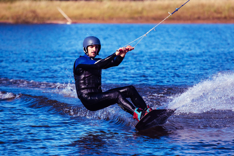 Portrait of young man wakeboarding in sea