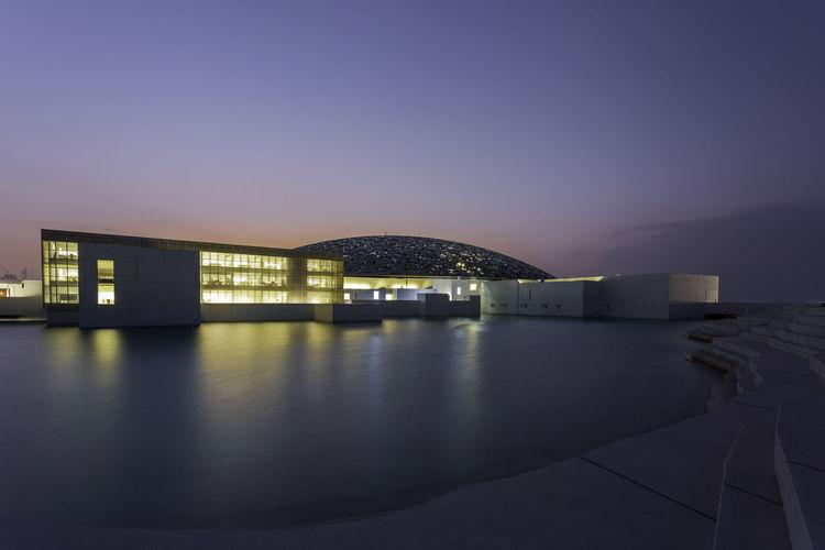 Illuminated modern building by sea against clear sky at dusk