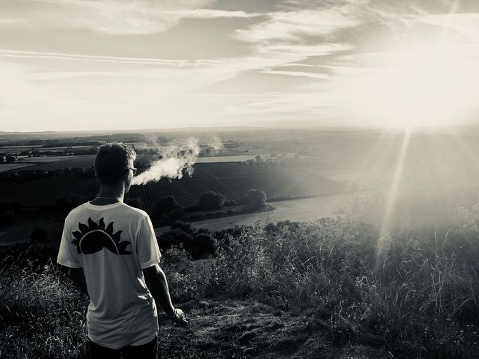 Rear view of man exhaling smoke while standing on hill looking at landscape against sky during sunset