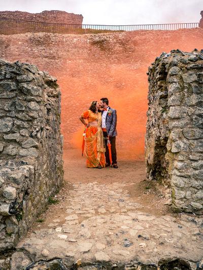Couple Kissing Against Concrete Wall