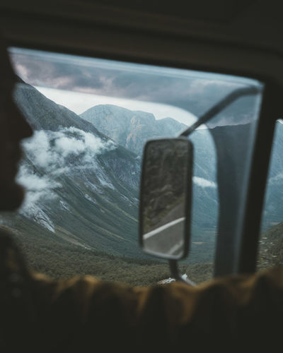 Man in vehicle against snowcapped mountains