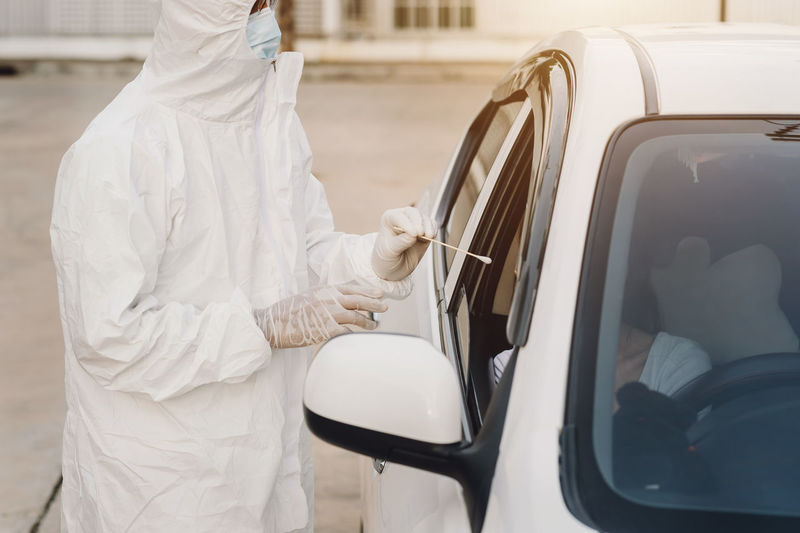 Midsection of man holding white car