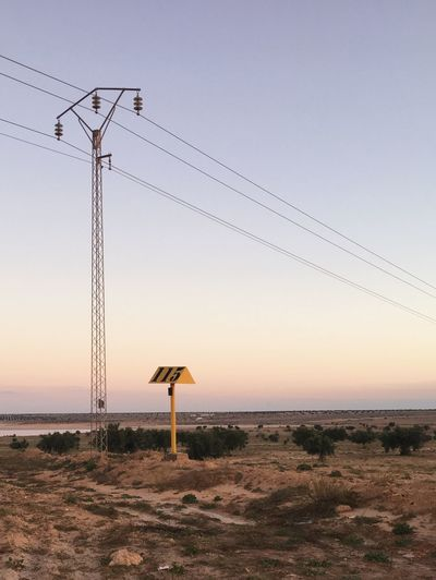 Electricity pylon on land against clear sky during sunset