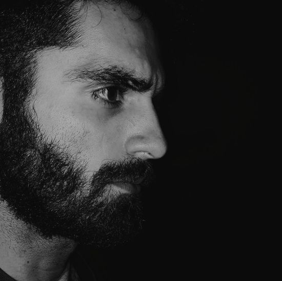 Side view of bearded man against black background