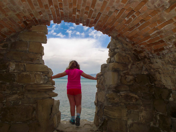 Rear View Of Girl Standing On Rock Against Sea