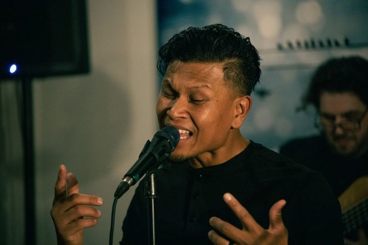 Mid adult man singing into a mic.