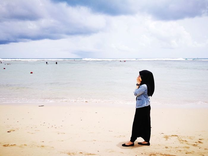 Side view of woman standing at beach against cloudy sky