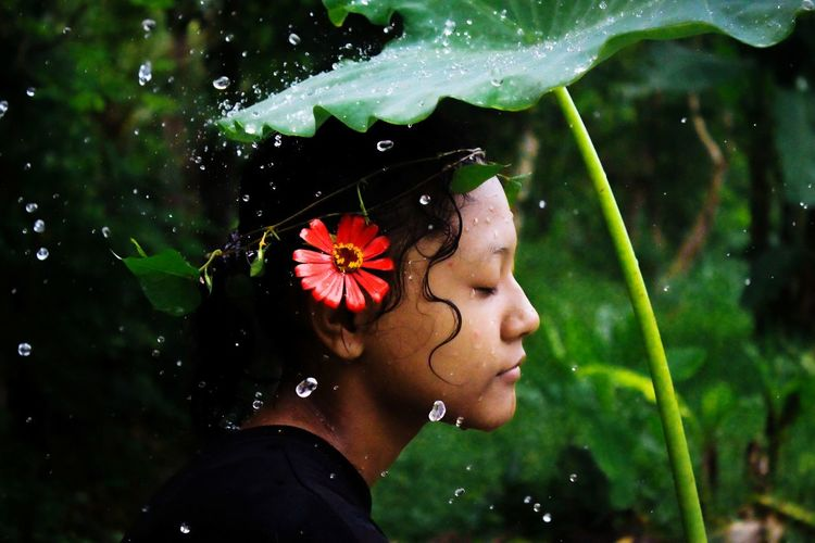 Close-up of teenage girl holding leaf during rainfall