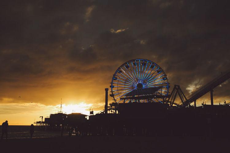 Silhouette Santa Monica Pier By Amusement Park Against Cloudy Sky During Sunset