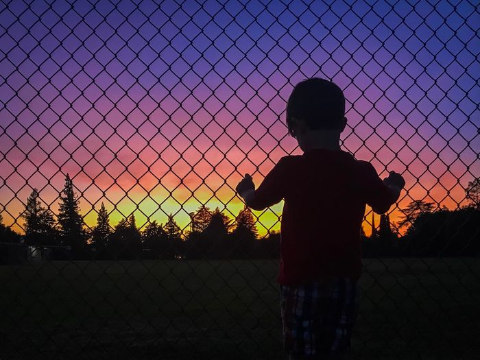 Rear View Of Silhouette Boy Standing By Fence Against Sky During Sunset