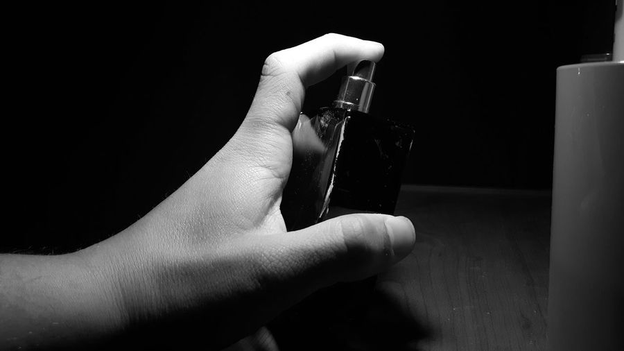 Cropped hand holding perfume bottle on table