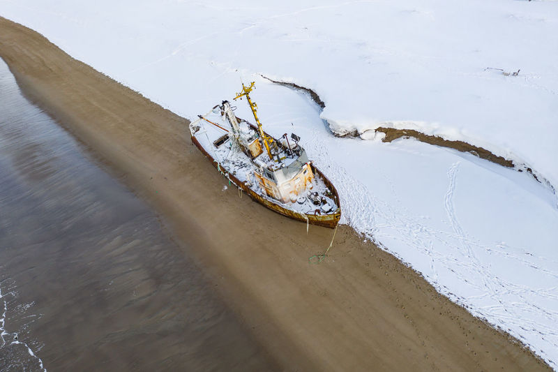 High angle view of abandoned boat on snow covered land