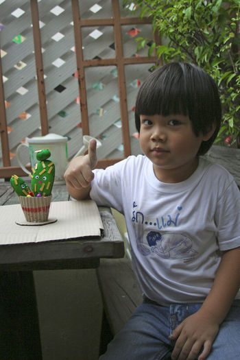 Portrait of boy showing thumbs up
