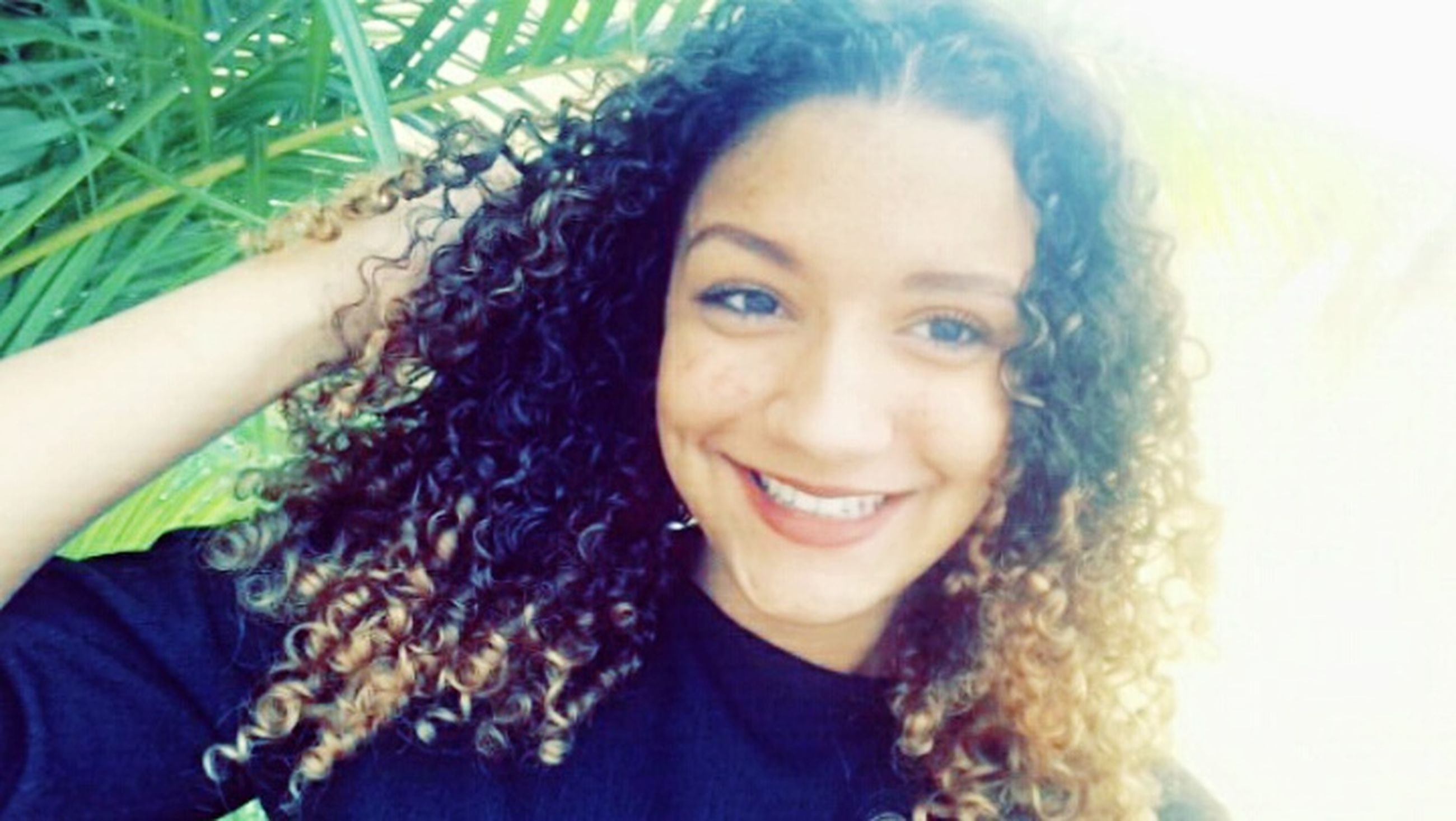 portrait, looking at camera, smiling, headshot, cheerful, happiness, only women, young adult, one woman only, one person, human body part, one young woman only, adults only, close-up, relaxation, people, sunlight, serene people, adult, outdoors, young women, females, women, beautiful woman, human arm, curly hair, nature, day, freshness