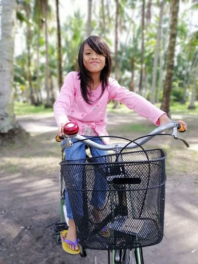 Portrait of woman riding bicycle on basket