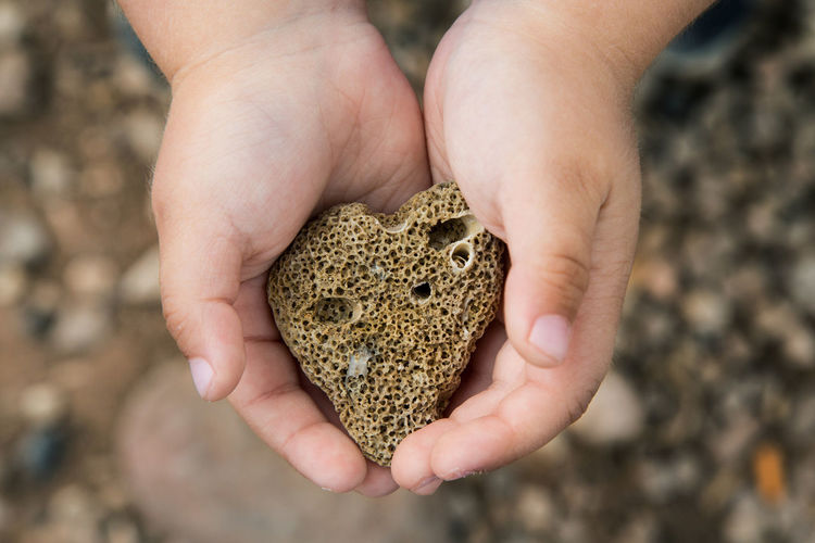 Photo of a heart-shaped stone in children's hands