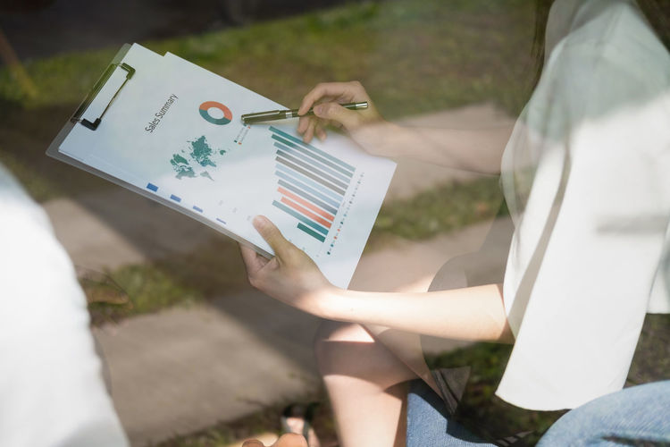 Midsection of businesswoman analyzing graphs in office