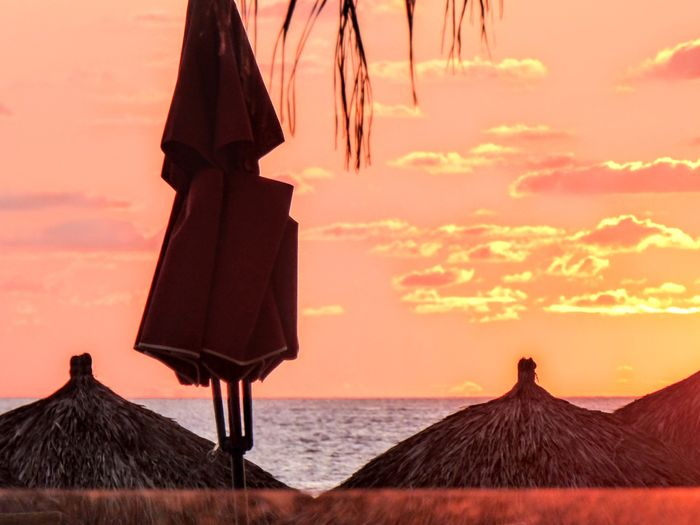 Getty Premium Collection Premium Sunset Sky Orange Color Thatched Roof Nature Outdoors Beauty In Nature Scenics Sea No People Day Beach Umbrella Palapa Silouette & Sky Yellow Sky Orange Sky Orange Sunset Orange Sky Sunset Yellow Sunset Shadows & Lights Water Selected For Premium Puerto Vallarta Puerto Vallarta, México Premium Collection