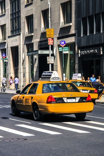 NY City Architecture Transportation Building Exterior Street Mode Of Transportation Car Motor Vehicle Road Built Structure Land Vehicle Sign City Street Motion Taxi Building City Life Yellow Incidental People Road Marking Outdoors
