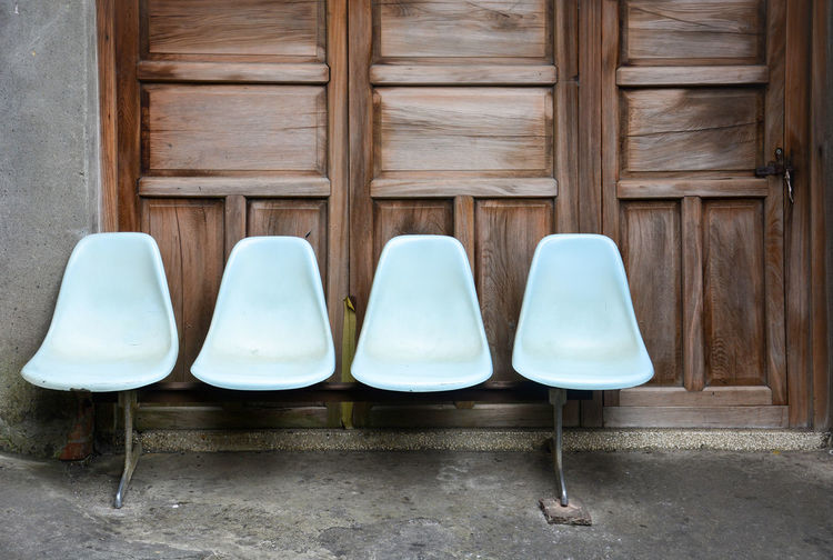 bench, row of old light blue plastic chairs on cement floor with wooden door background, lonely concept No People Absence Seat Empty Chair In A Row Architecture Door Wall Awaiting Backrest Bench Concept Dirty Old Retro Sit Stool Street Bus Stop Vintage Wait Wooden Backgrounds Bide