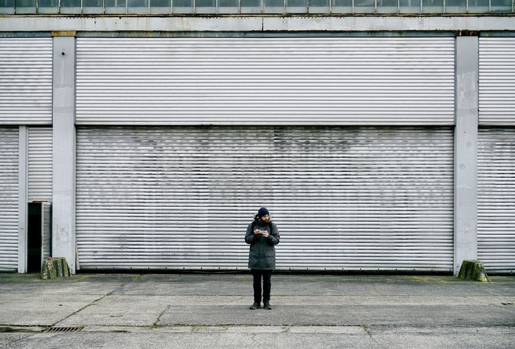 Man standing on footpath against building