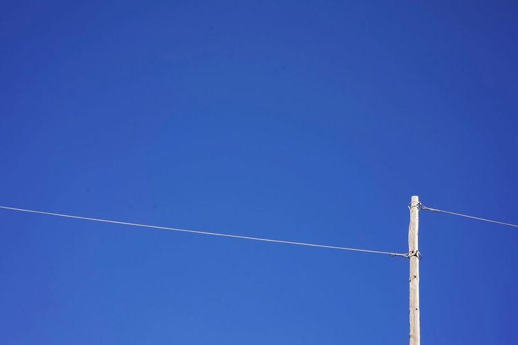 Electricity  Blue Sky Low Angle View Copy Space Clear Sky Day Vapor Trail No People Outdoors Metal Sunlight Connection Cable Power Supply Sunny